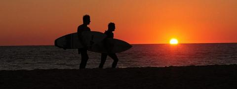 A picture of surfers walking on a beach in the sunset. By Sean Keenan