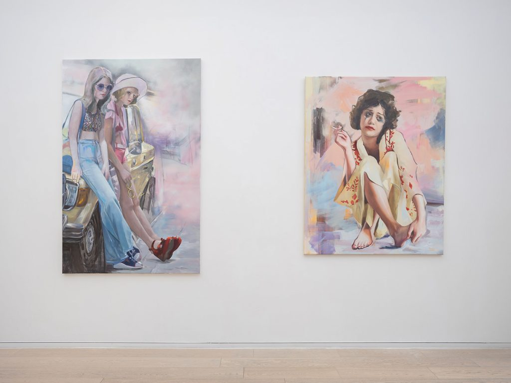 two portrait paintings hanging in a gallery