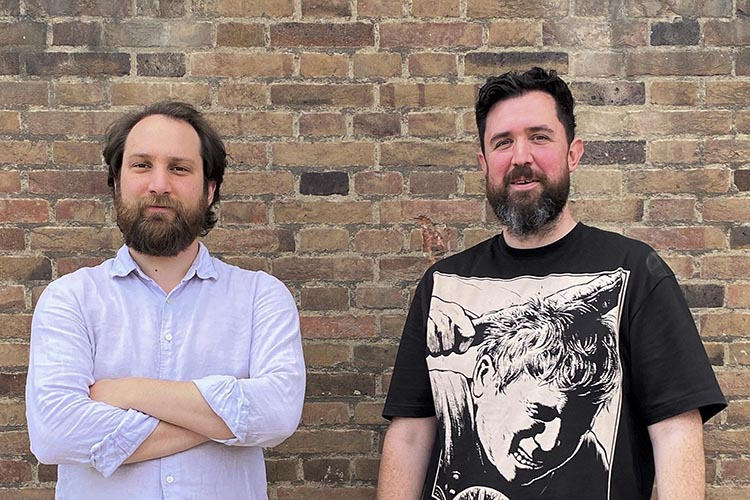 portrait of two men in front of a wall